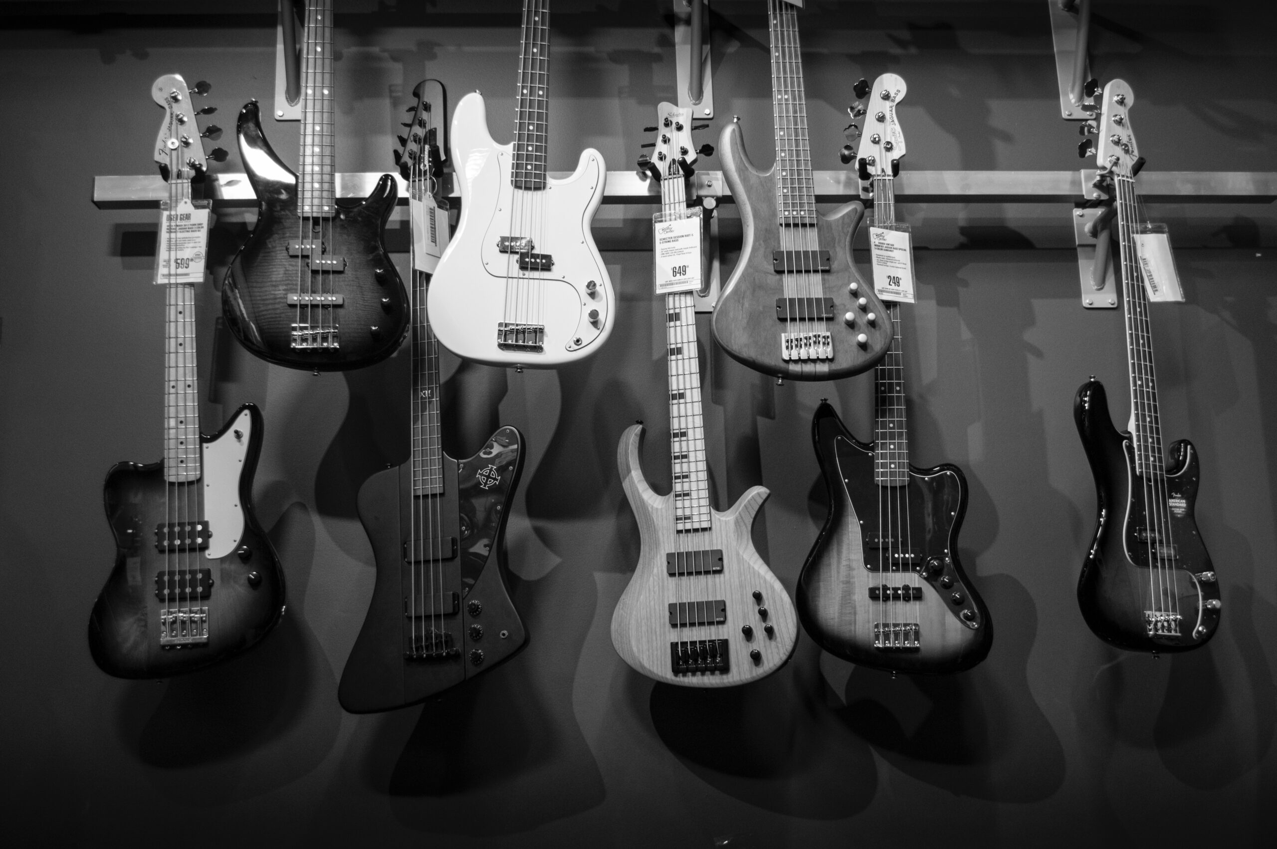Electric Guitars Hanged on Steel Bar | Bass Guitar for Beginners: A Definitive Guide To Learning