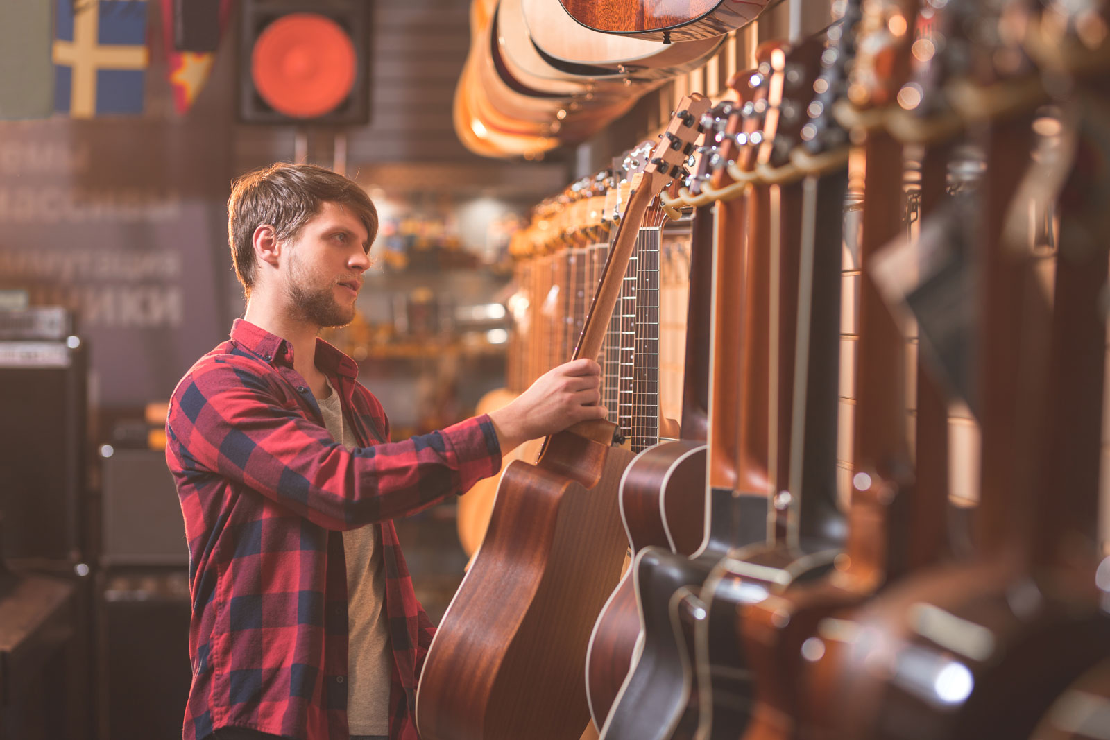 Man Choosing Guitar | 5 Differences in Learning to Play Electric Guitar Vs Acoustic