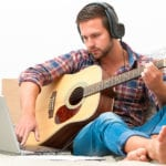 Man Playing Guitar Wearing Earphones | 3 Simple Steps to Teach Yourself Guitar Chords Today