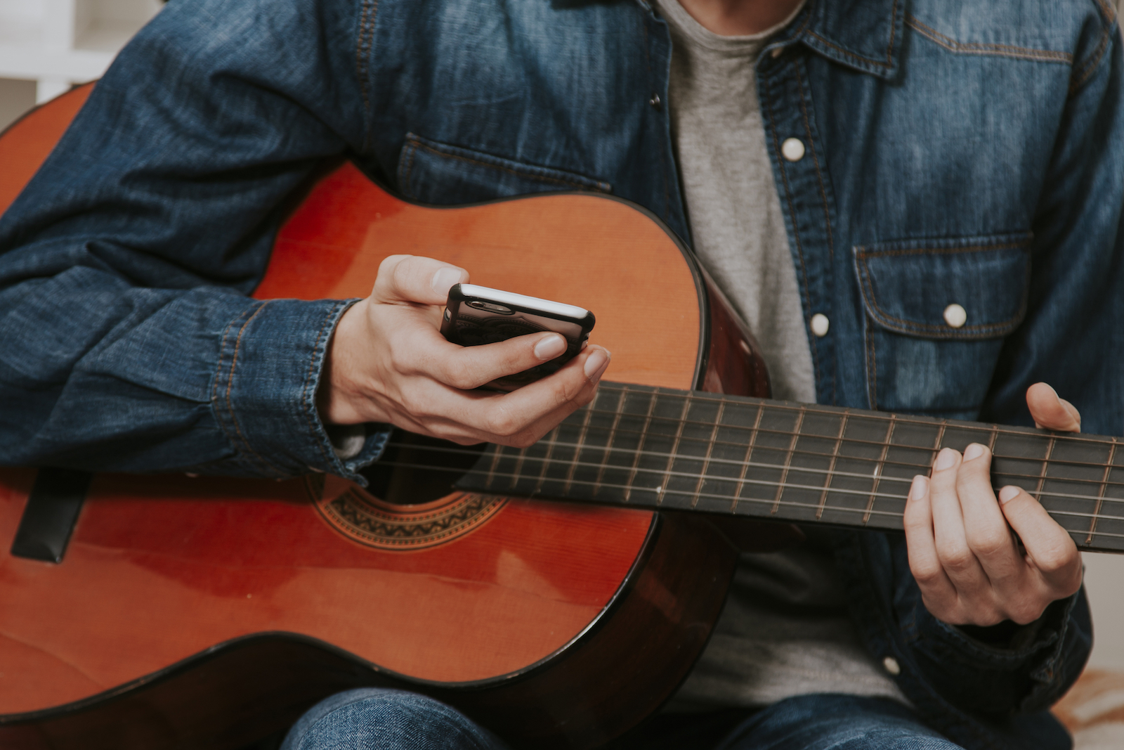 Man Playing Guitar Holding a Mobile Phone | 3 Simple Steps to Teach Yourself Guitar Chords Today