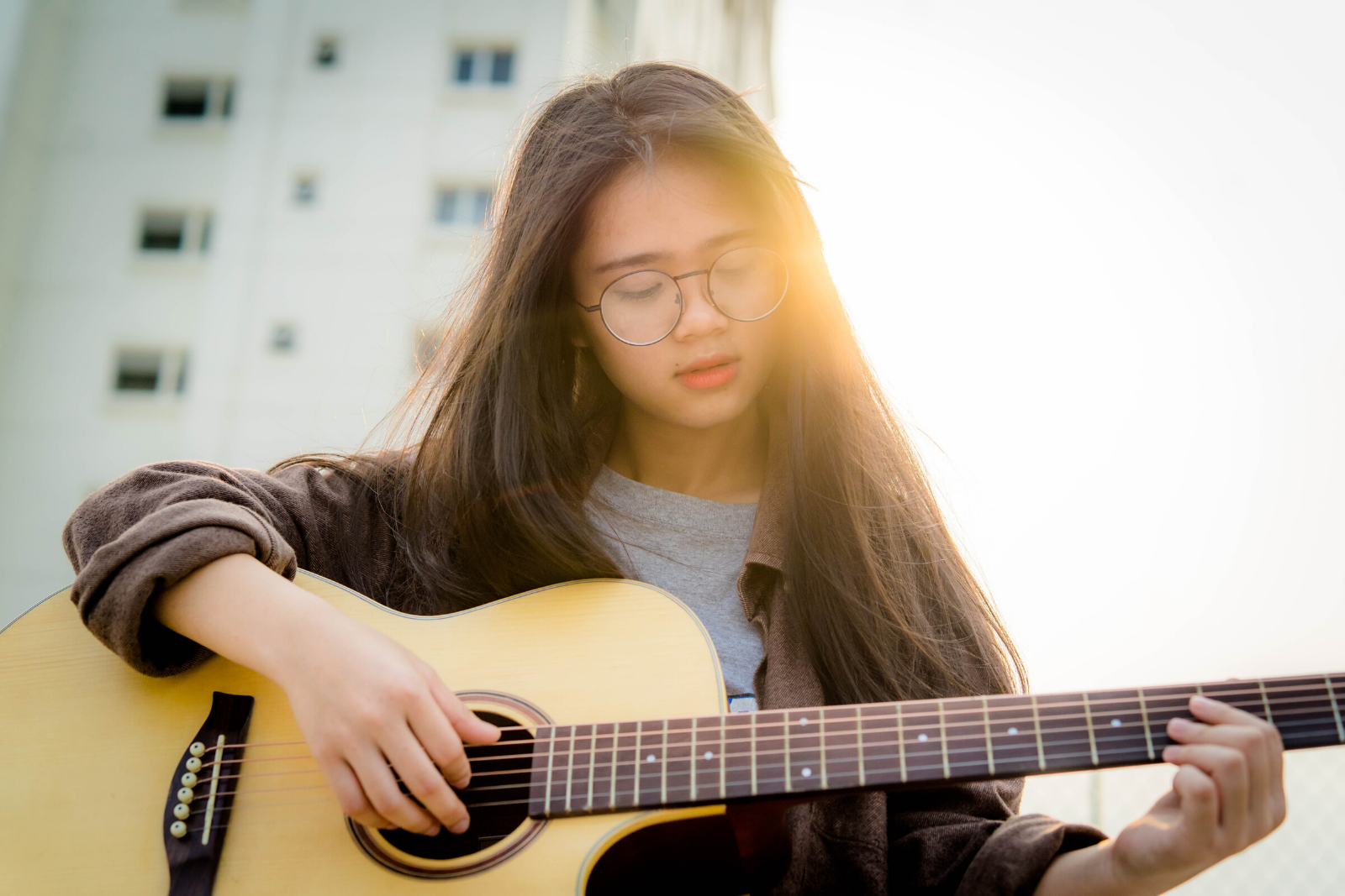 Girl Playing Guitar | Which Is The Easiest Guitar To Learn For Beginners?