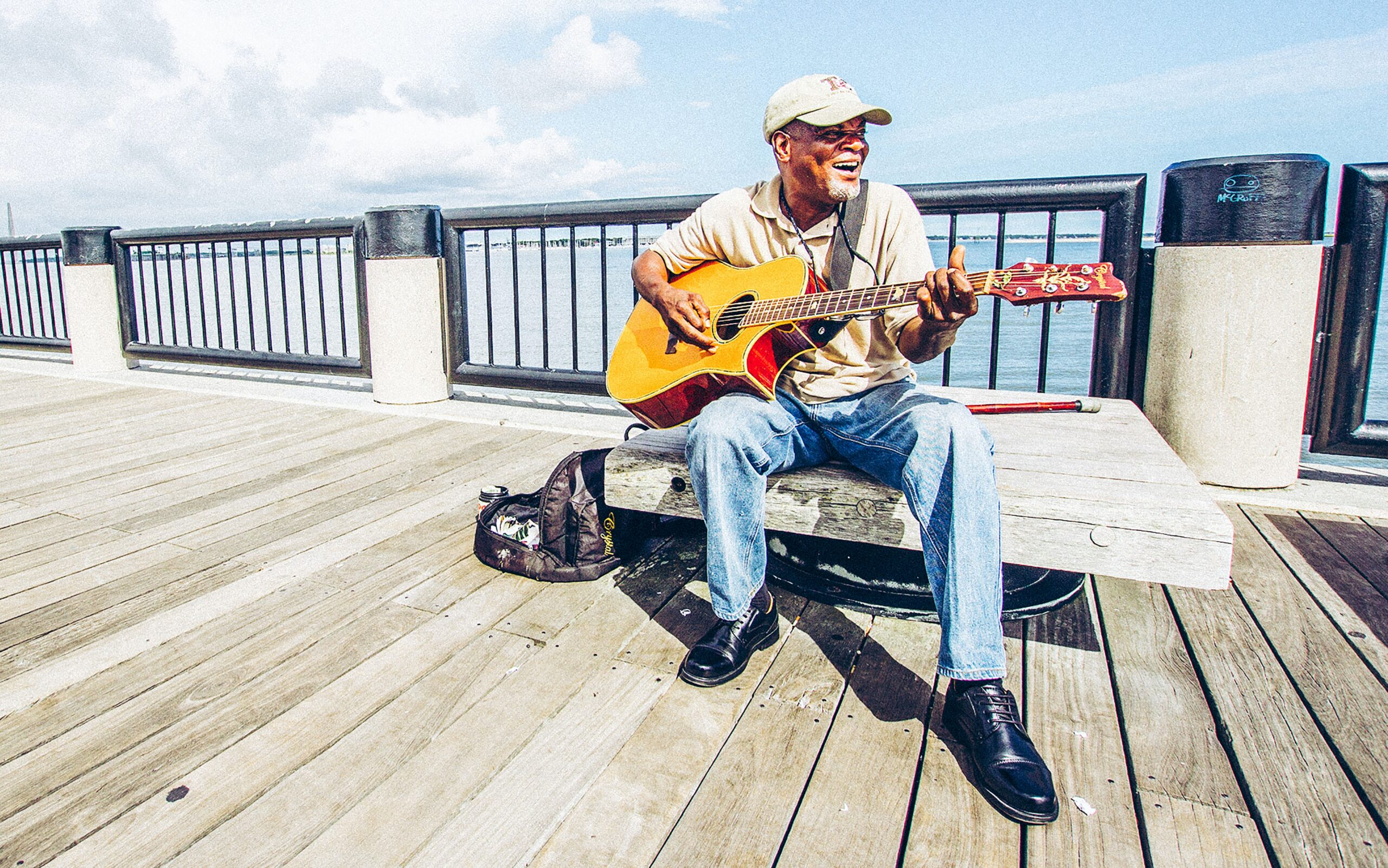 Man Sitting On Bench While Playing Guitar   10 Simple Ways To Find The Best Guitar Lessons
