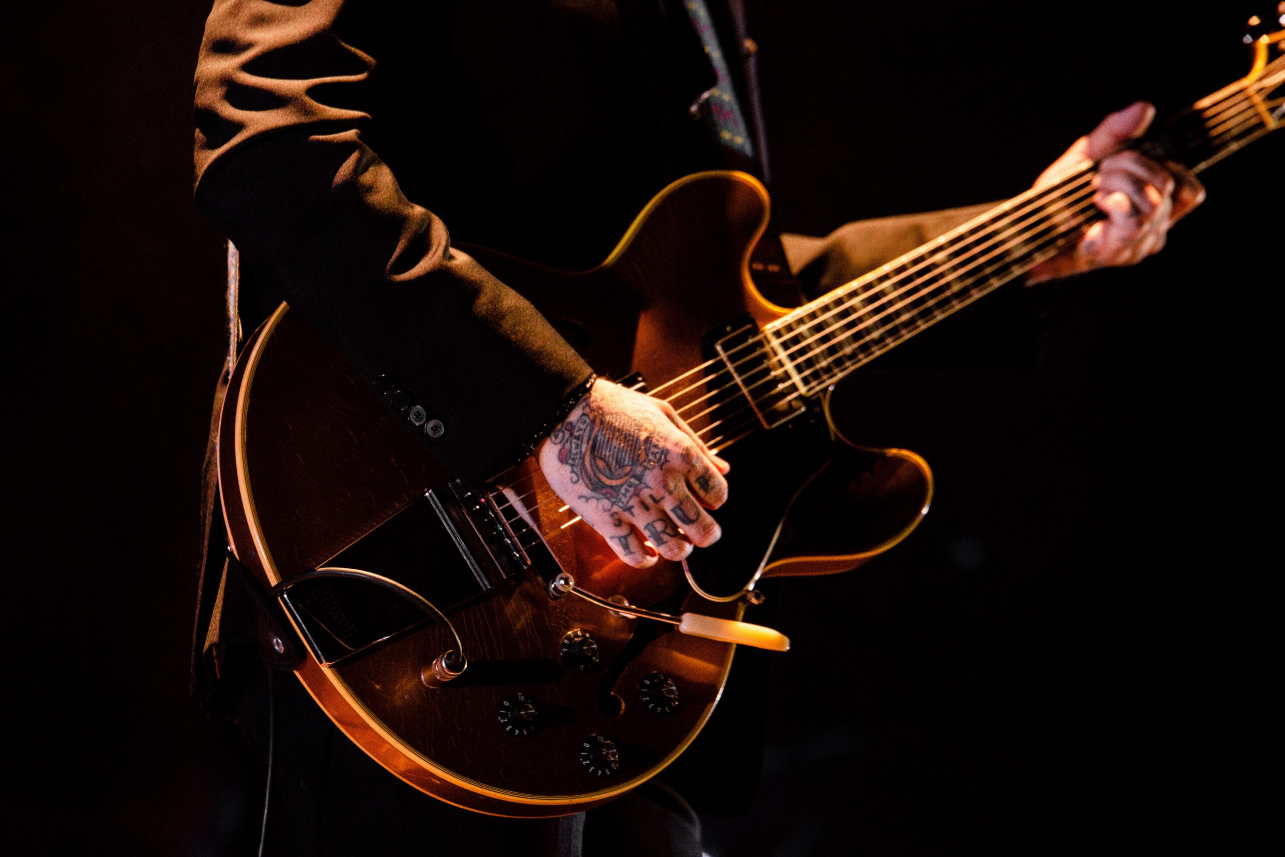 Person Playing Guitar | Top 9 Milestones To Shoot For When Learning To Play Guitar