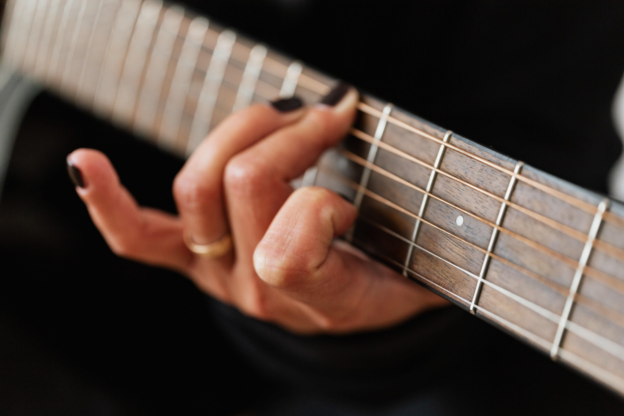 Woman Touching Strings of Guitar   10 Simple Ways To Find The Best Guitar Lessons