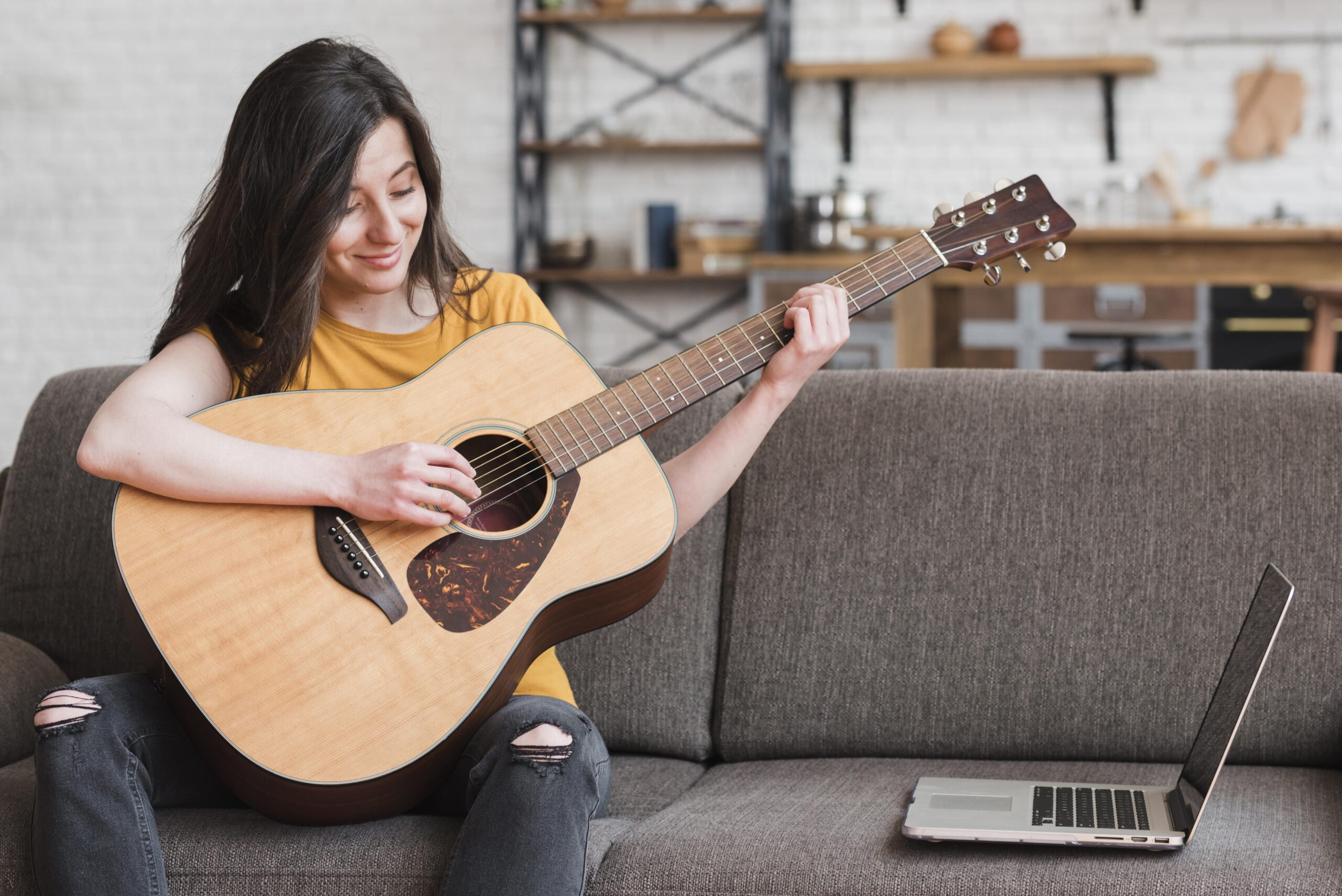 Woman Learning Online How To Play Guitar | Guitar Tricks vs JamPlay: Which one is better for you?