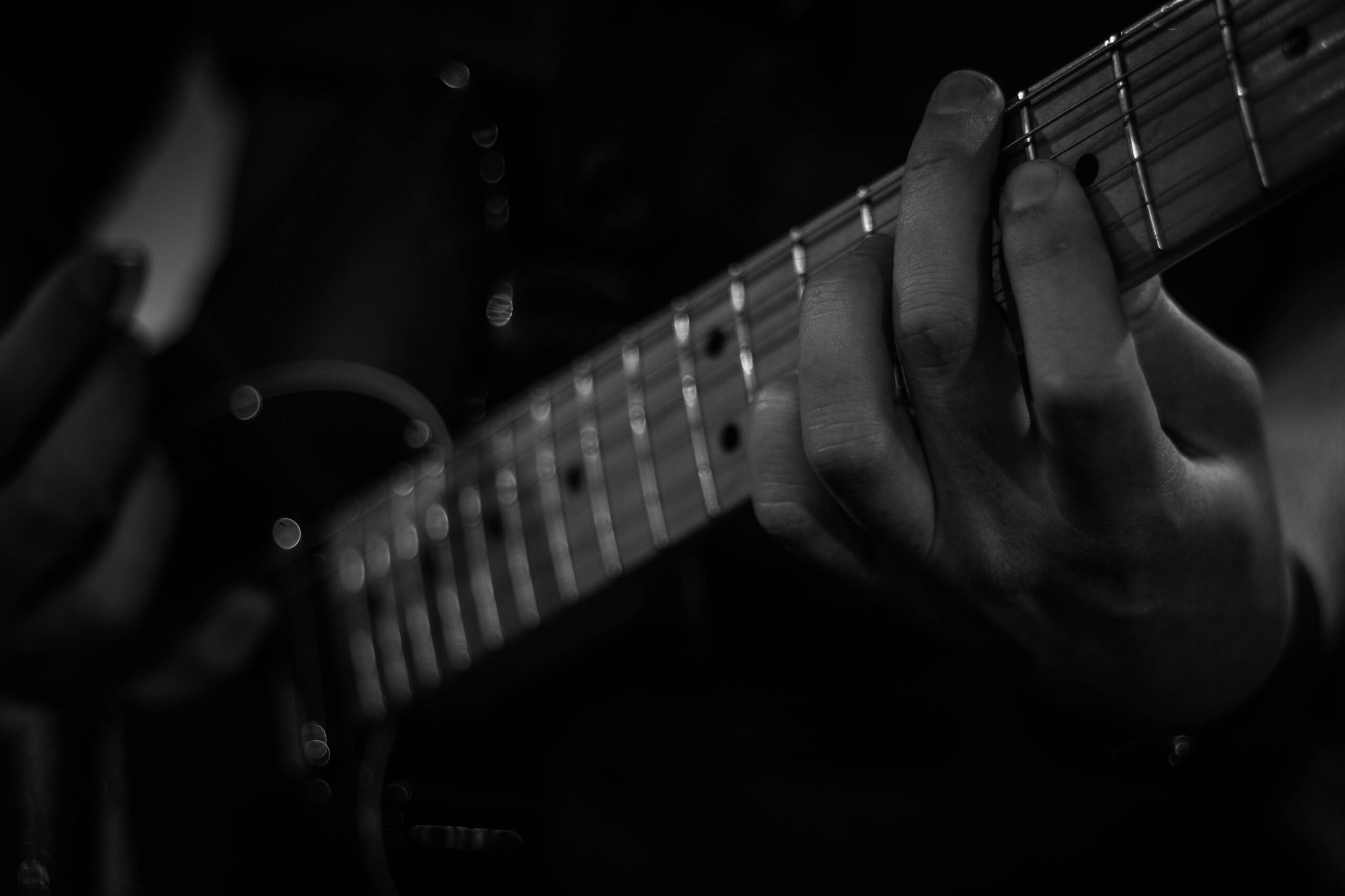 Person Playing Guitar Grayscale | 7 Tested Solutions To Help You Learn Guitar Through Video Games